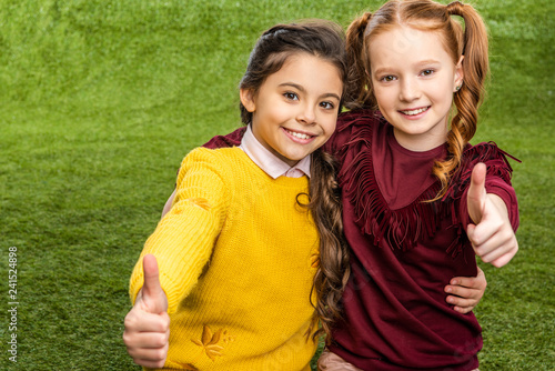 smiling schoolgirls looking at camera and showing thumbs up on lawn