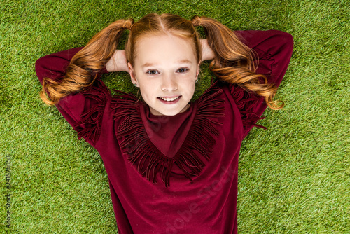 top view of smiling schoolgirl with hands on head looking at camera and lying on lawn