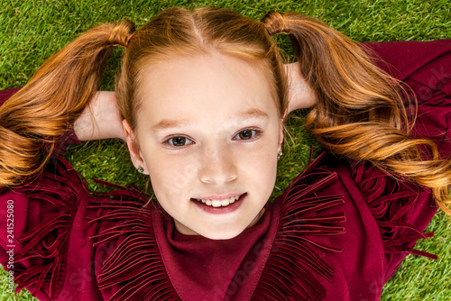 top view of cute schoolgirl with hands on head lying on lawn and looking at camera
