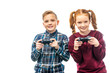 smiling kids holding gamepads and looking at camera isolated on white