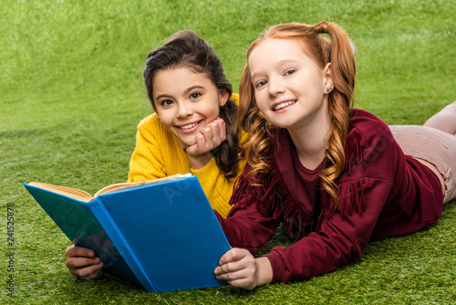 smiling schoolgirls lying on lawn, holding book and looking at camera