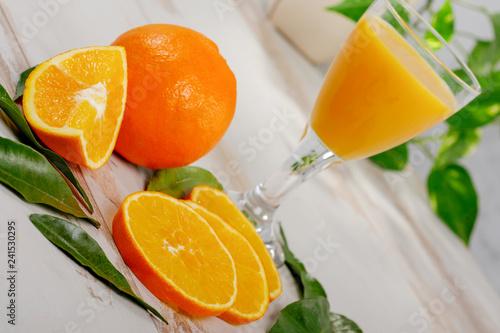 orange and glass of orange juice on white wooden table