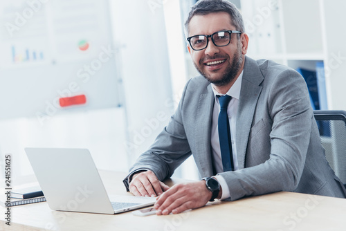 cheerful businessman in eyeglasses using laptop and smiling at camera in office