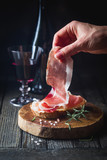 Female hand putting prosciutto on bread over dark wooden background. Sandwich cooking.