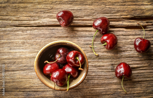 Two heart shape red cherry fruits with the stems winded together with other fruits scattered around and some in ceramic cup.