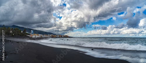Landscape of mountains and ocean with cloudy sky and black beach. - 241557277