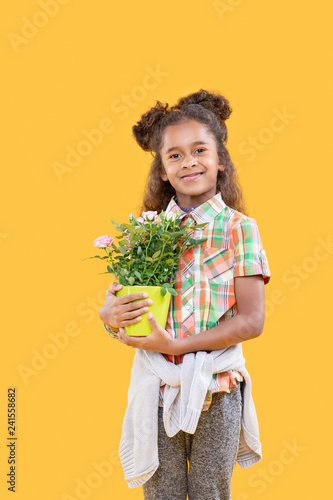 Cheerful delighted girl holding her favourite flower