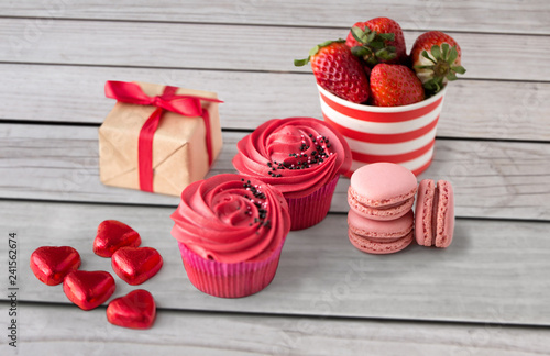 valentines day and sweets concept - close up of frosted cupcakes, red heart shaped chocolate candies, macarons, strawberries and gift box - 241562674