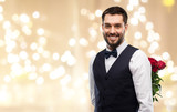 valentines day, greeting people concept - happy man in party clothes with red roses behind his back over festive lights background - 241562846