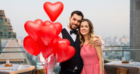 valentines day, love and people concept - happy couple with red heart shaped balloons over restaurant lounge in singapore city background