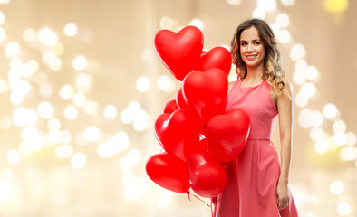 valentines day, love and people concept - happy young woman with red heart shaped balloons over festive lights background
