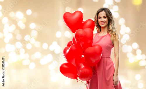 Leinwanddruck Bild valentines day, love and people concept - happy young woman with red heart shaped balloons over festive lights background