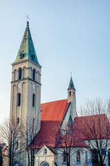 The Roman Catholic Church of Saint Michael the Archangel in Olesno, Poland. With square tower and steeple and arch windows.