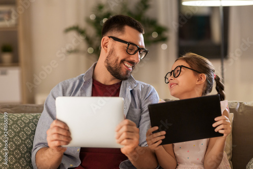family, fatherhood and technology concept - happy father and daughter in glasses with tablet pc computers at home © Syda Productions