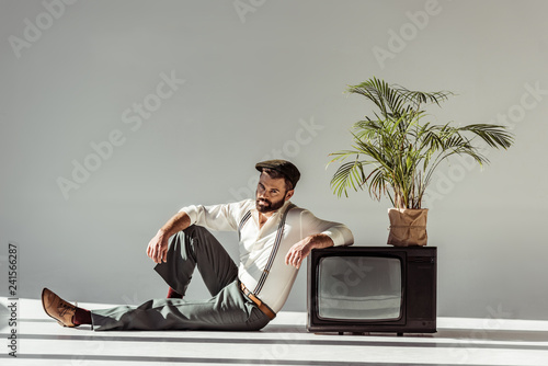 handsome bearded man in cap sitting on floor near vintage tv with plant in pot and looking at camera