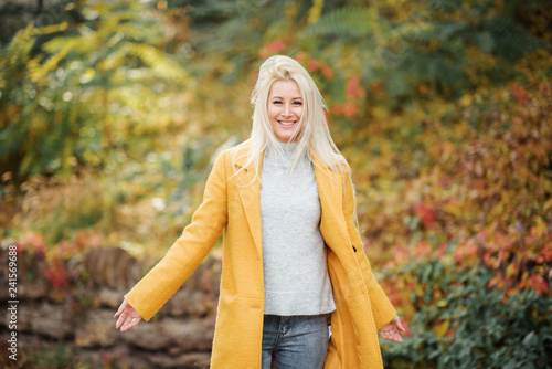 Leinwanddruck Bild Fashion lifestyle portrait of young happy blond woman laughing and having fun in the city park at nice sunny day. bright fresh colors