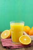 Colorful composition with mason jar glass full of fresh orange juice with straw, fruit, isolated on green background. Close up, copy space, top view.