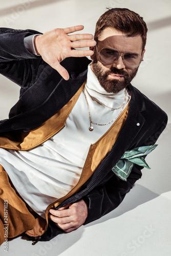 Foto Murales handsome bearded man lying on floor with hand against sunlight