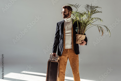 handsome bearded man in glasses holding green plant in pot and vintage suitcase on grey background