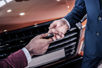 Rich successful man taking keys from his new car from sales manager