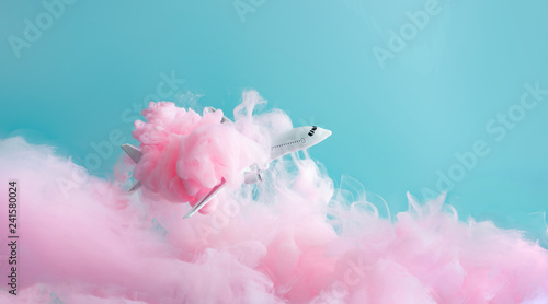Passenger jet airplane flying through pastel pink clouds. Minimal transportation, travel or vacation concept. - 241580024