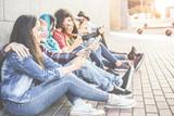 Millennial friends using smartphones sitting outdoor  - 241580272