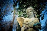 Beautiful sad angel. Vintage styled image of ancient statue.