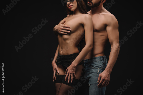 cropped view of sexy man hugging nude breast of beautiful girlfriend, isolated on black