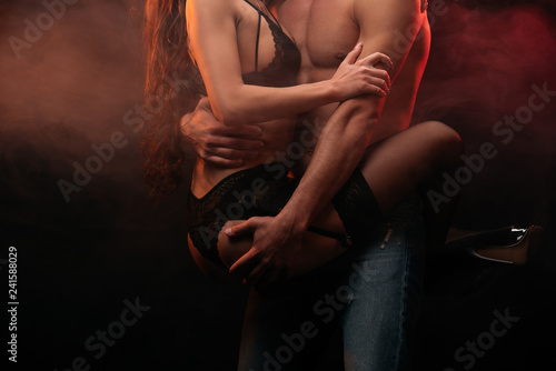 Leinwandbild Motiv cropped view of passionate couple hugging in smoky room