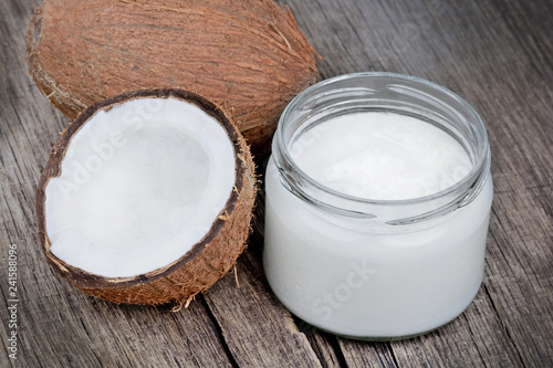Coconut oil and fresh coconuts on old table
