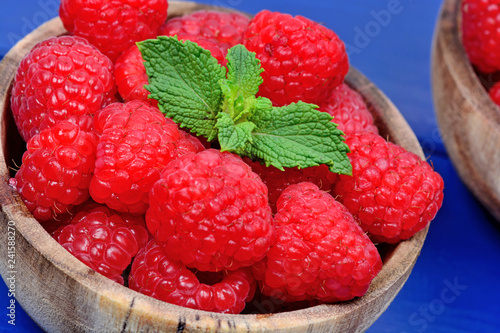 Foto Murales Raspberries in a bowls on a wood table