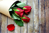 Close up of a bouquet of red roses over wooden background with copy space - 241593098