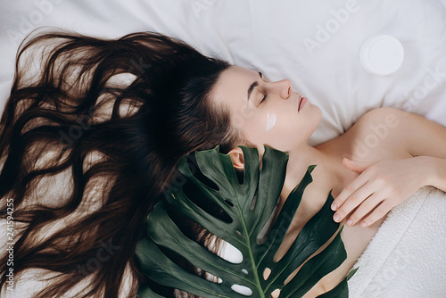 Attractive young long-haired girl applying cream on her face lying on the bed with a green leaf enjoying and relaxing , day spa . Skin care and beauty concept.