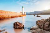 Leuchtturm am Meer am Ufer mit Bergen beim Sonnenuntergang - 241600280