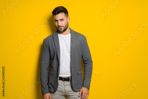 Leinwandbild Motiv Young handsome man possing and modeling over yellow isolated background