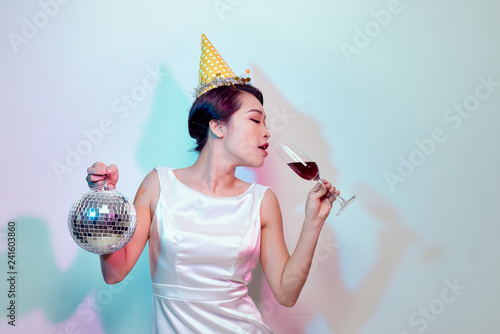 Portrait of a happy beautiful woman in white dress having a party and drinking champagne while standing with disco ball isolated over light background - 241603860