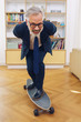 Playful businessman practicing on a skateboard