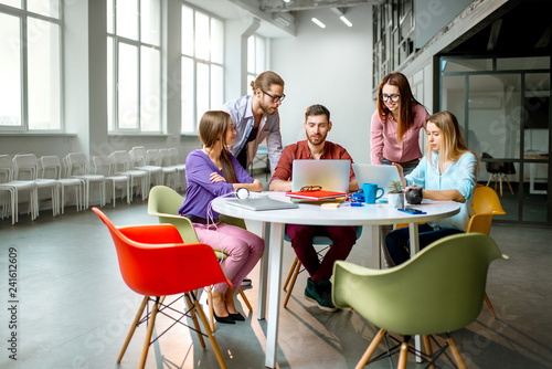 Group of a young coworkers dressed casually working together with laptops in the modern office