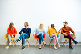 Portrait of a young people dressed casually sitting in a row on the colorful chairs on the white wall background - 241613407