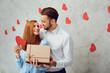 Leinwandbild Motiv A young couple gives a gift on a gray background.
