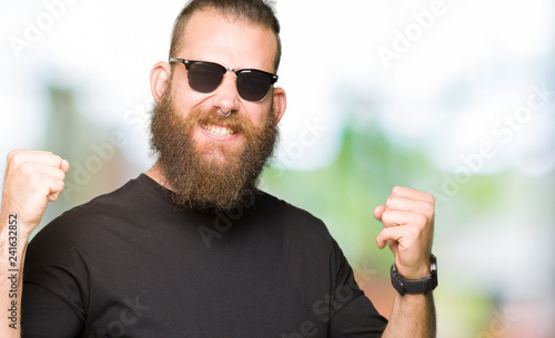 Leinwanddruck Bild Young hipster man wearing sunglasses very happy and excited doing winner gesture with arms raised, smiling and screaming for success. Celebration concept.