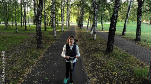 Girl from school ride a scooter in park in autumn.