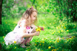 A girl with long curly hair in a long white dress collects dandelions in spring. Happy baby on a walk. Kids without gadgets.