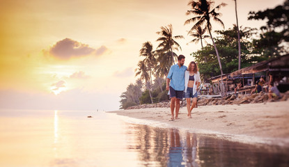 Beautiful young love happy couple walking arm in arm on the beach at sunset during the honeymoon vacation travel © olezzo