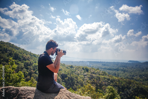 Handsome young stylish male photographer of mixed race in a black T-shirt with a camera in hand on top of a mountain with a view