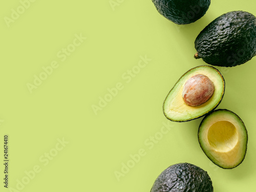 Fresh organic hass avocados on a green background, top view with copy space - 241674410