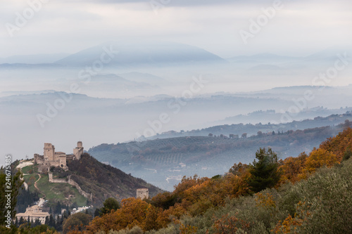 Leinwandbild Motiv Beautiful view of Rocca Maggior castle (Assisi, Umbria, Italy) over a sea of fog with distant hills in the background and orange and green trees in the foreground