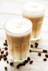 Two glasses of latte coffee and coffee beans