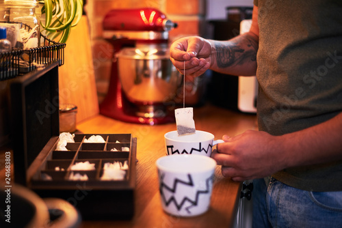 Young man making tea in kitchen