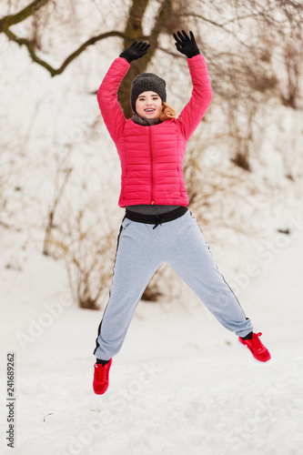 Woman wearing sportswear exercising outside during winter - 241689262